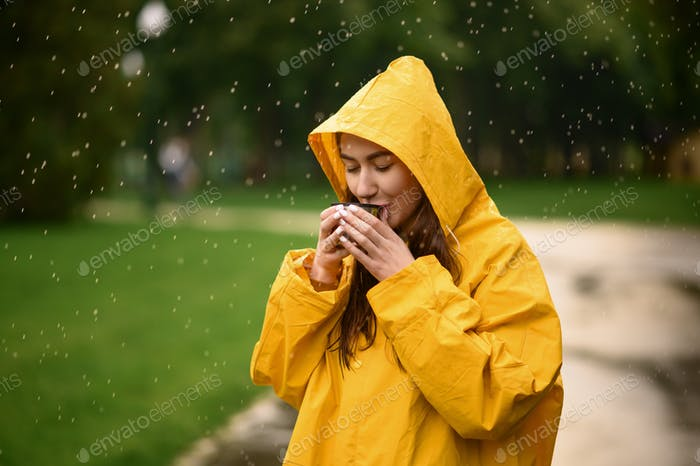 Woman in raincoat drinks hot tea in park, rainy