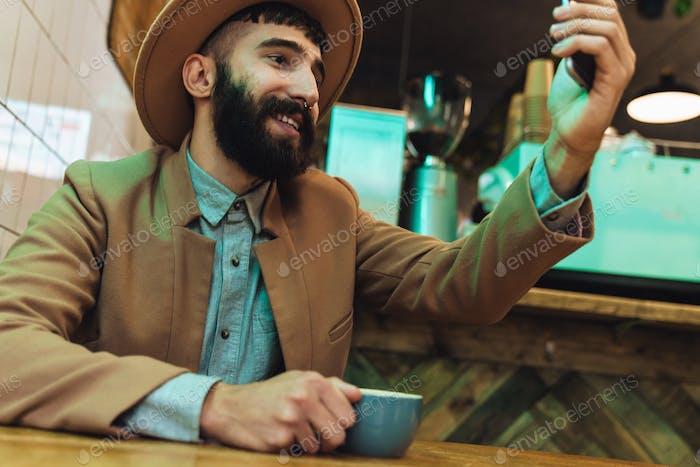 Imagen de un joven atractivo con sombrero usando el teléfono celular en el café