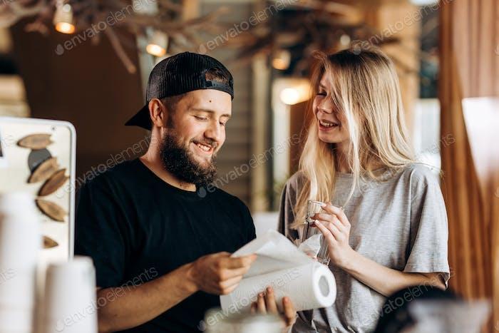 Dos Gente sonrientes, una chica rubia y un Hombre con barbuda.vestido con traje casual, pararse al lado de