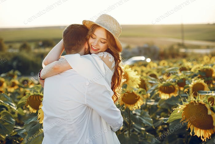 Schönes und stilvolles Paar in einem Feld wirh Sonnenblumen
