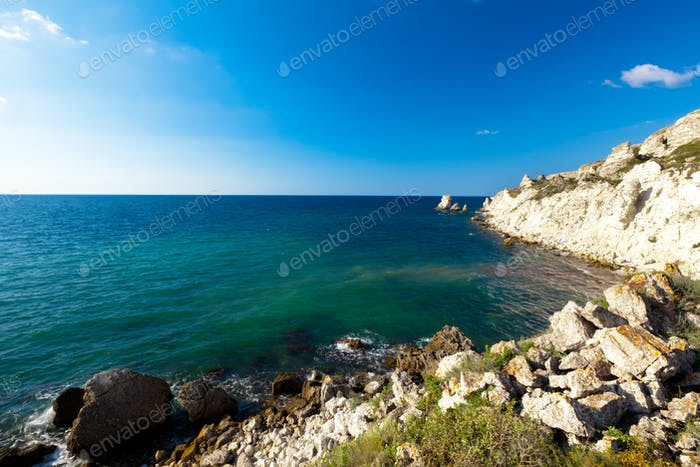 Seascape of still blue sea waters shore, rocky coastline and bright sun