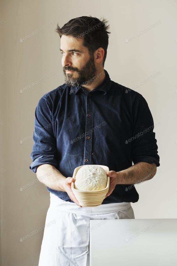 Bäcker hält einen frisch gebackenen Laib Weißbrot in einem Rattan-Proofing Korb.