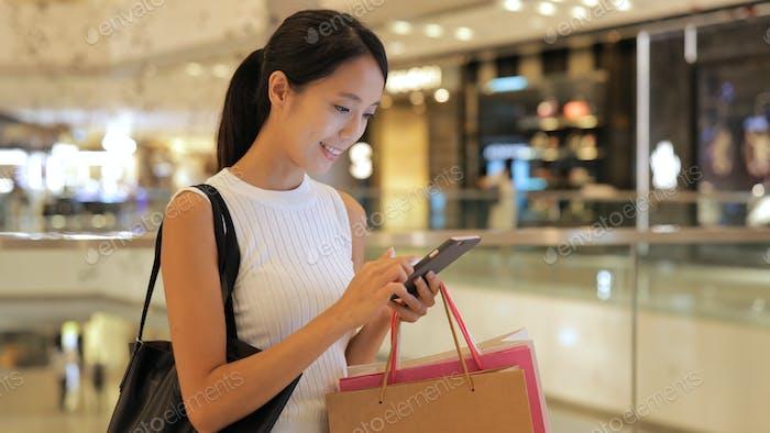 Frau mit Handy und halten Einkaufstaschen im Einkaufszentrum
