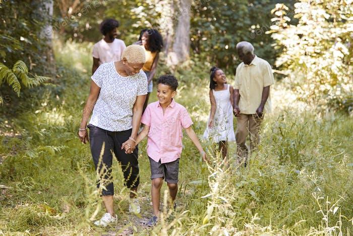 Black grandma walking with grandson and family, full length