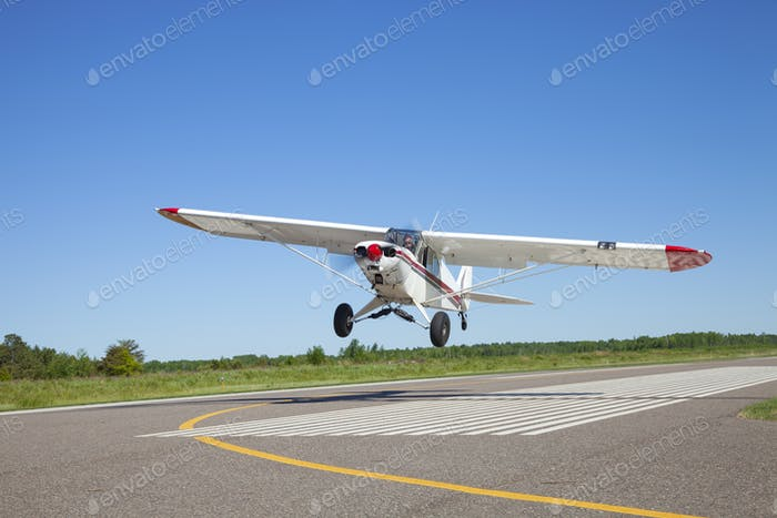 Small airplane takes off from a municipal airport on a sunny afternoon