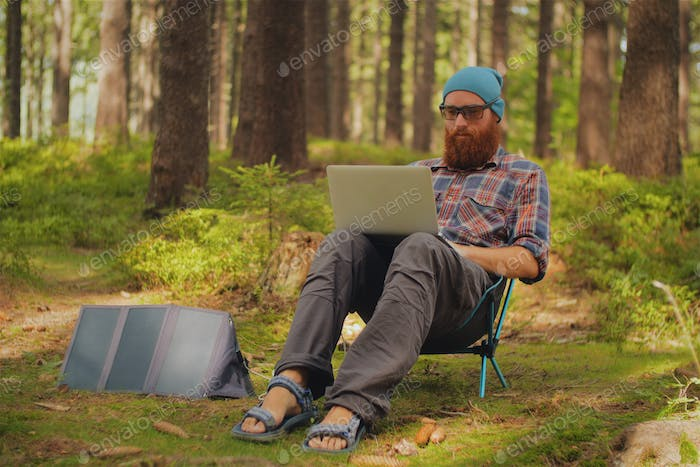 man using a laptop outdoors during a camping trip, digital nomad, work on the road