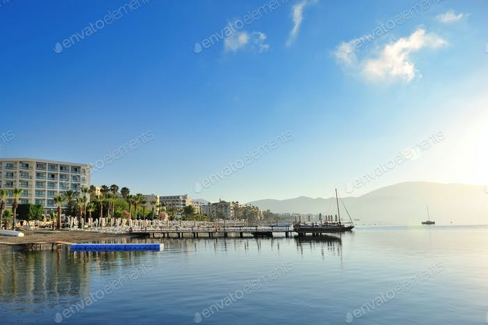 Beautiful morning seascape with boats and mountains in the backg
