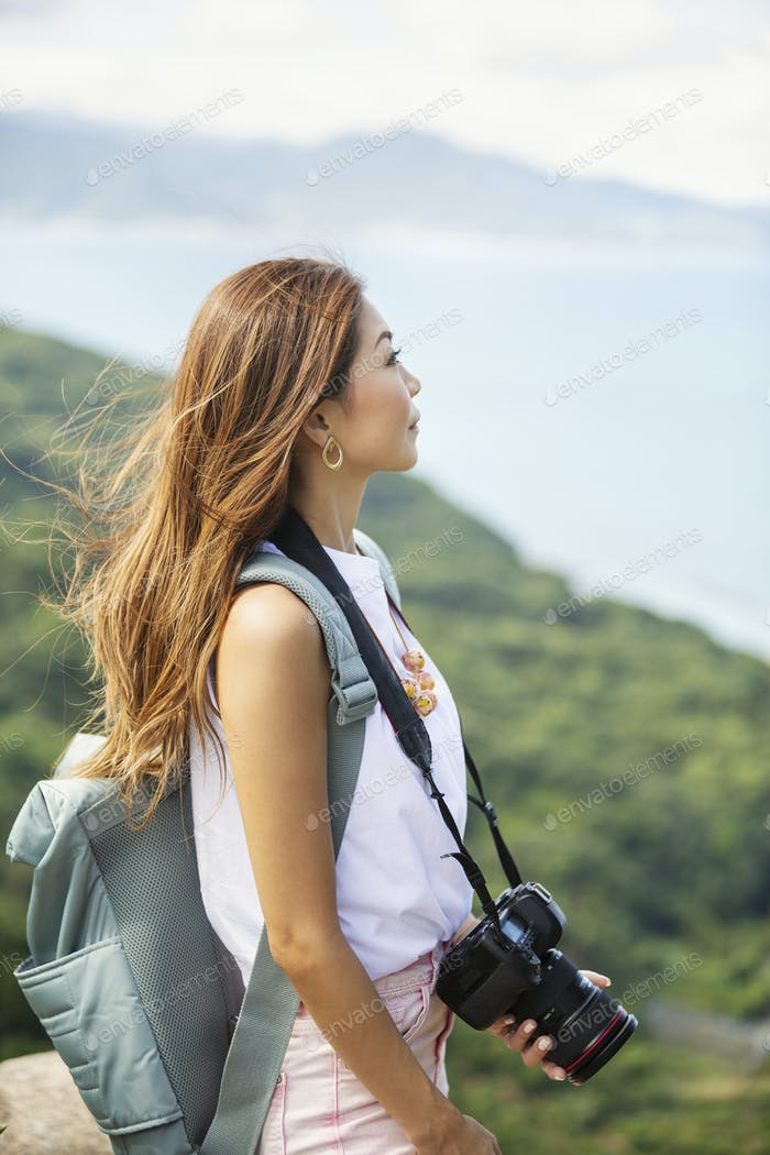 Japanese woman carrying backpack and holding camera standing on a cliff, ocean in the background.