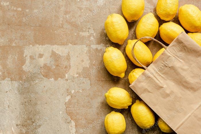 Draufsicht von Zitronen und Papiertüte auf verwitterter Oberfläche