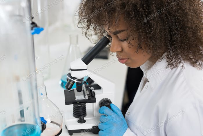 Young Scientist Looking Through Microscope In Laboratory, Mix Race Researcher Doing Research