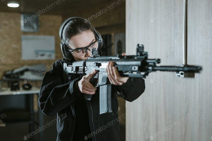 Mädchen zielt Gewehr auf Schießstand