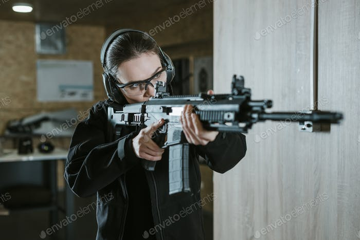 girl aiming rifle in shooting range