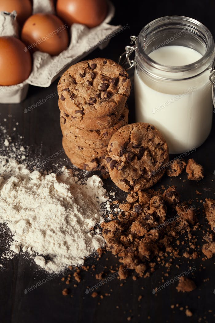 Homemade chocolate chip cookies with bottle of milk, white flour and crumbs