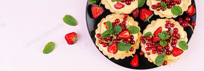 Tarts with strawberries, currant and whipped cream decorated wit