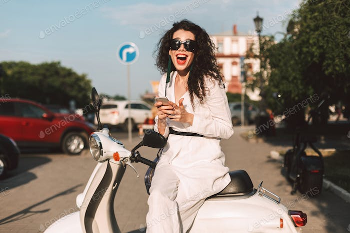 Cheerful stylish girl sitting on moped with cellphone happily looking in camera in city center