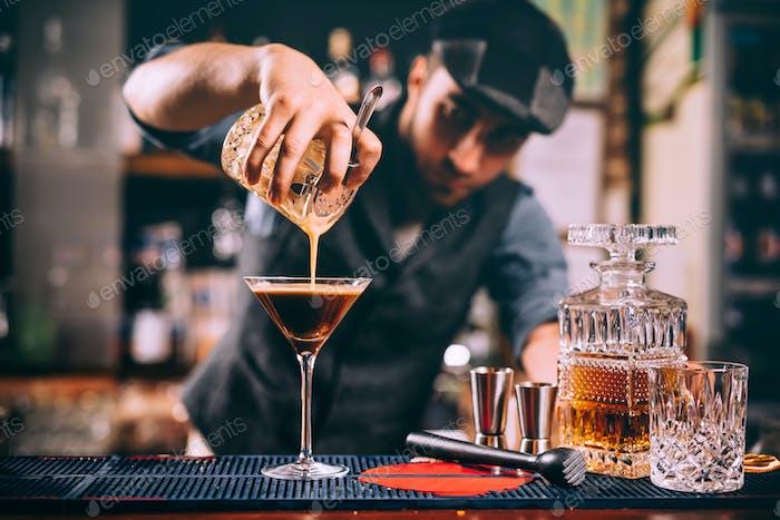 Porträt von professionellen Barkeeper Vorbereitung alkoholischer Getränke an der Bar
