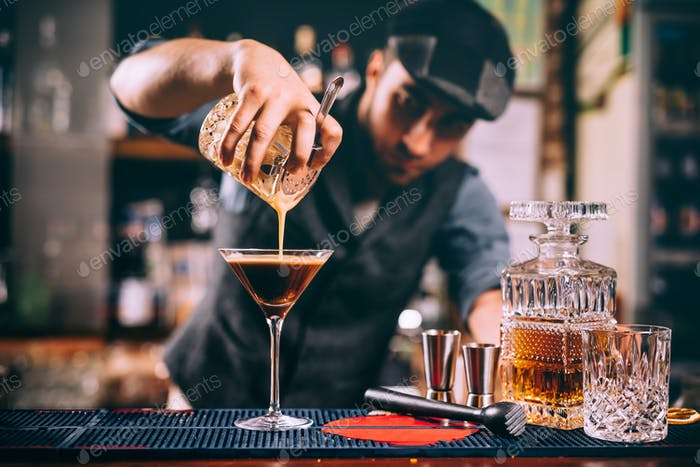 Portrait of professional bartender preparing alcoholic drinks at bar