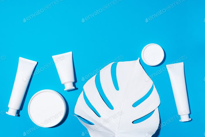 White bottles of skin care creams, monstera leaf over blue background with copy space. Top view