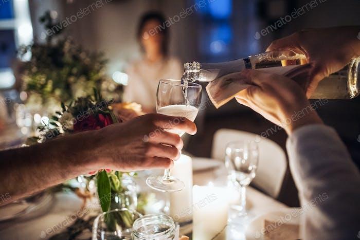 Ein Mittelteil des Kellners, der Champagner in ein Glas auf einer Indoor-Party in der Nacht gießt.