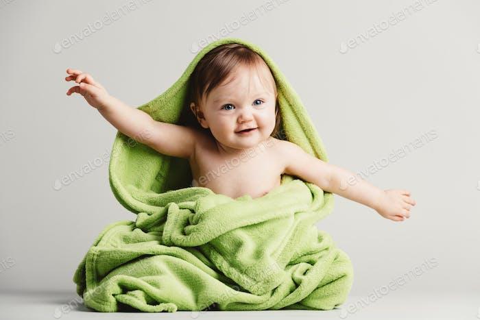 Ребенок покрыт зеленым одеялом в смешной позе.