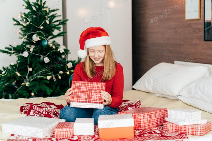 Teenage girl opens boxes with Christmas gifts in Advent.