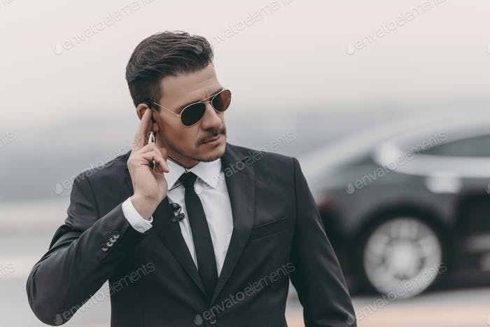 handsome bodyguard listening message with security earpiece