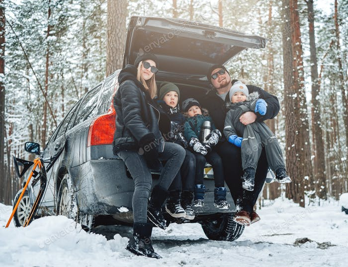 Snowy forest and caucasian family posing on car trunk in daytime