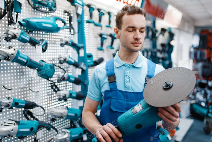 Male worker holds angle grinder in tool store