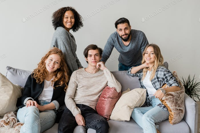 Group of happy young intercultural friends in casualwear relaxing on soft couch