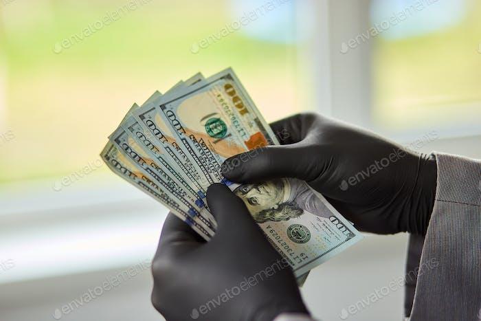 Man holding money dollars in hand in black medical gloves.