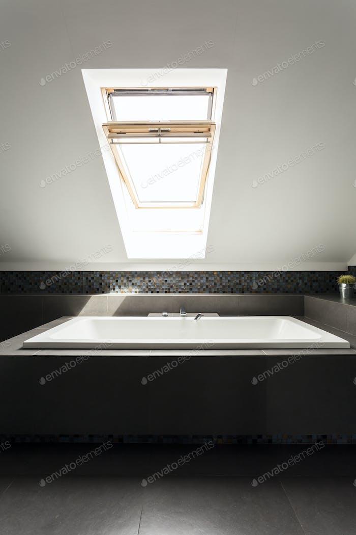 Прямоугольная ванна под окном чердака