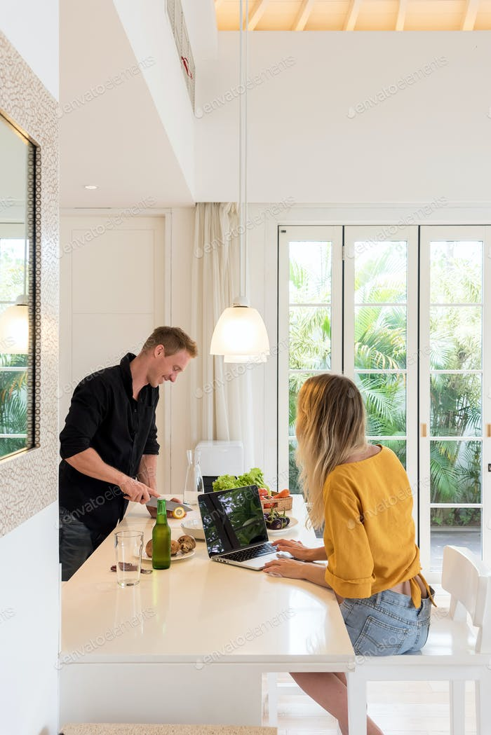 Couple making lunch on a white kitchen at home