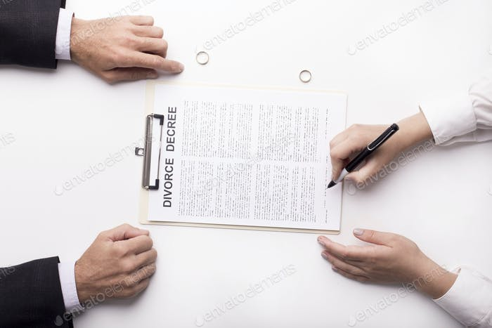 Hands of wife signing decree of divorce, dissolution, canceling marriage