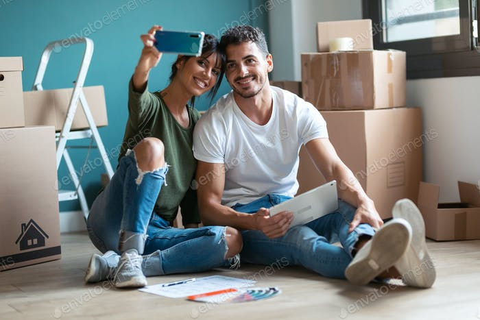 couple taking a picture of themselves while looking ideas to decorate the new apartment