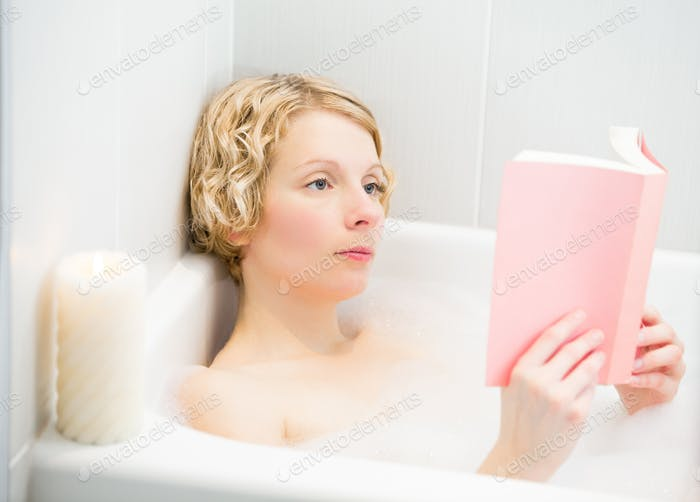 Young woman relaxing and reading a book in the bath
