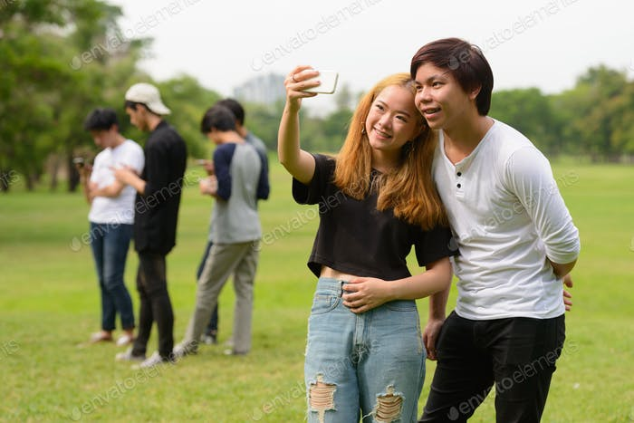 Happy young Asian couple taking selfie together with friends at the park