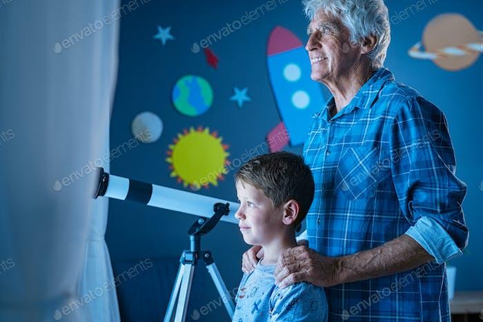 Großvater und Enkel schauen nachts aus dem Fenster