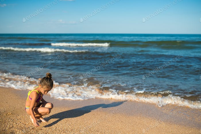 Little lonely girl writes something on the sand
