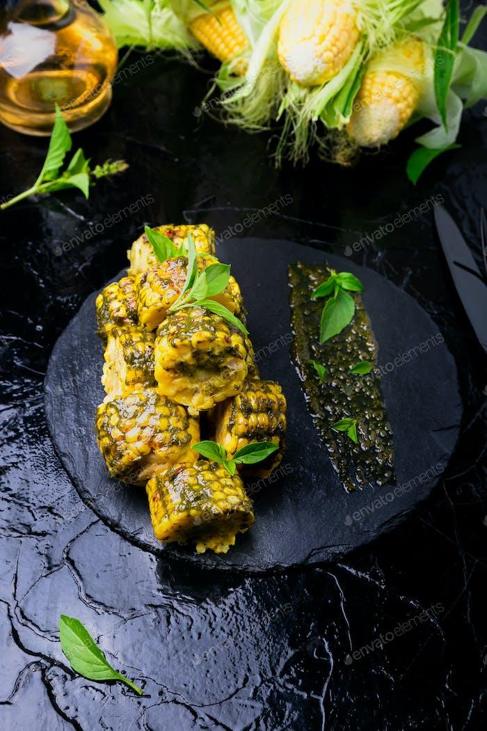Grilled corn with sauce pesto on black slate plate. Close up.  Vegan food.