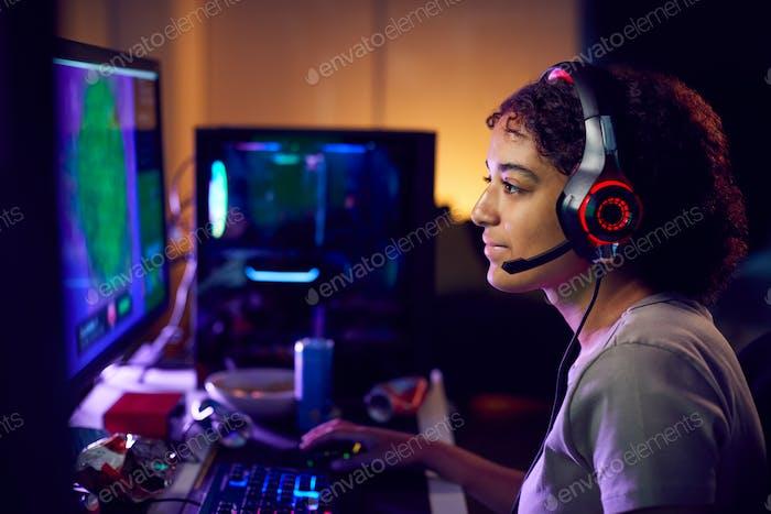 Teenage Girl Wearing Headset Gaming At Home Using Dual Computer Screens