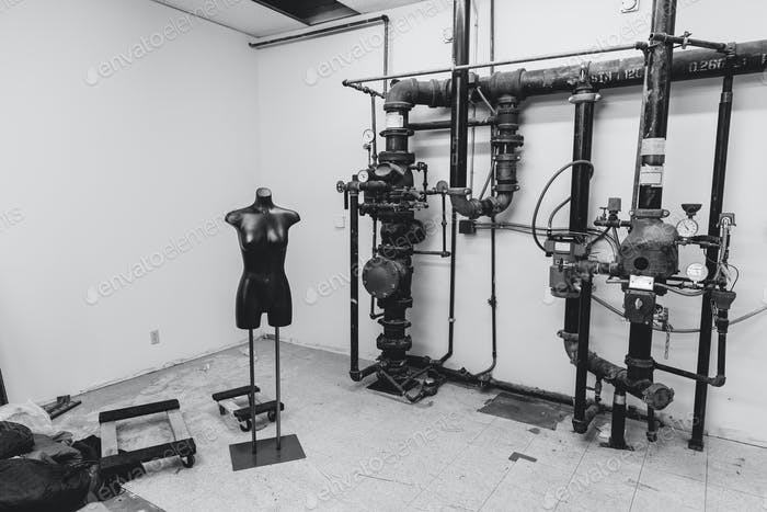 A mannequin next to industrial pipework inside a room.
