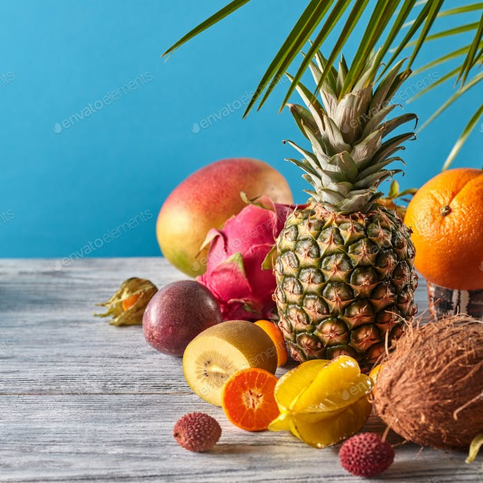 Exotic mix from ripe fruits - pineaple, dragon fruit, mango, coconut, kiwi, carambola, litchi on a