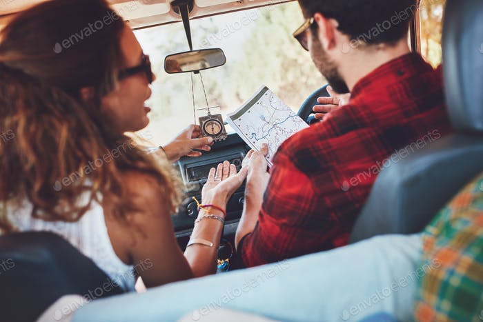 Couple using map on a roadtrip to decide which way to go