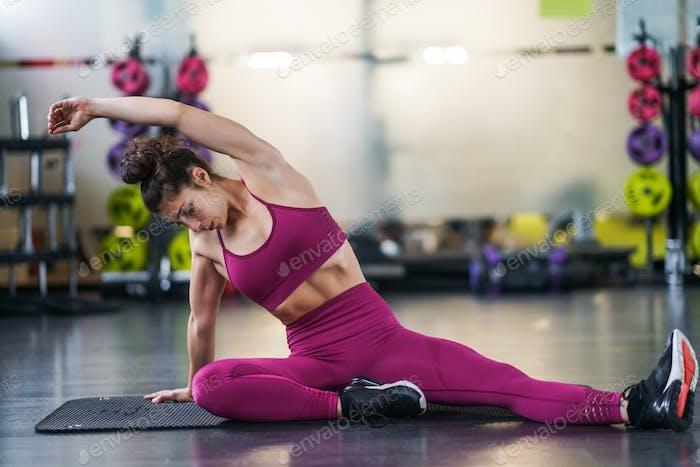 Junge Frau tun Dehnübungen auf einer Yoga-Matte