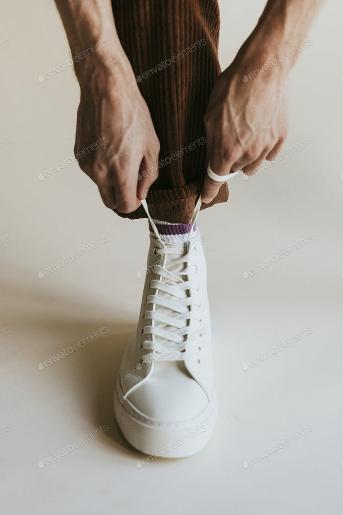 Man hands fixing shoelaces white high top shoes