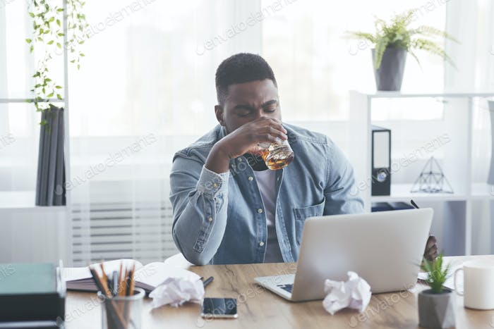 Tired african american employee drinking alcohol at workplace