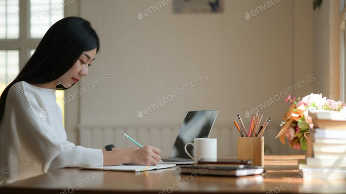 Cropped shot of Asian student girl preparing a project for thesis to graduate with determination.