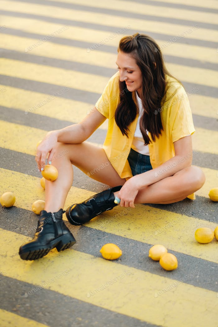 a girl with lemons in a yellow shirt,