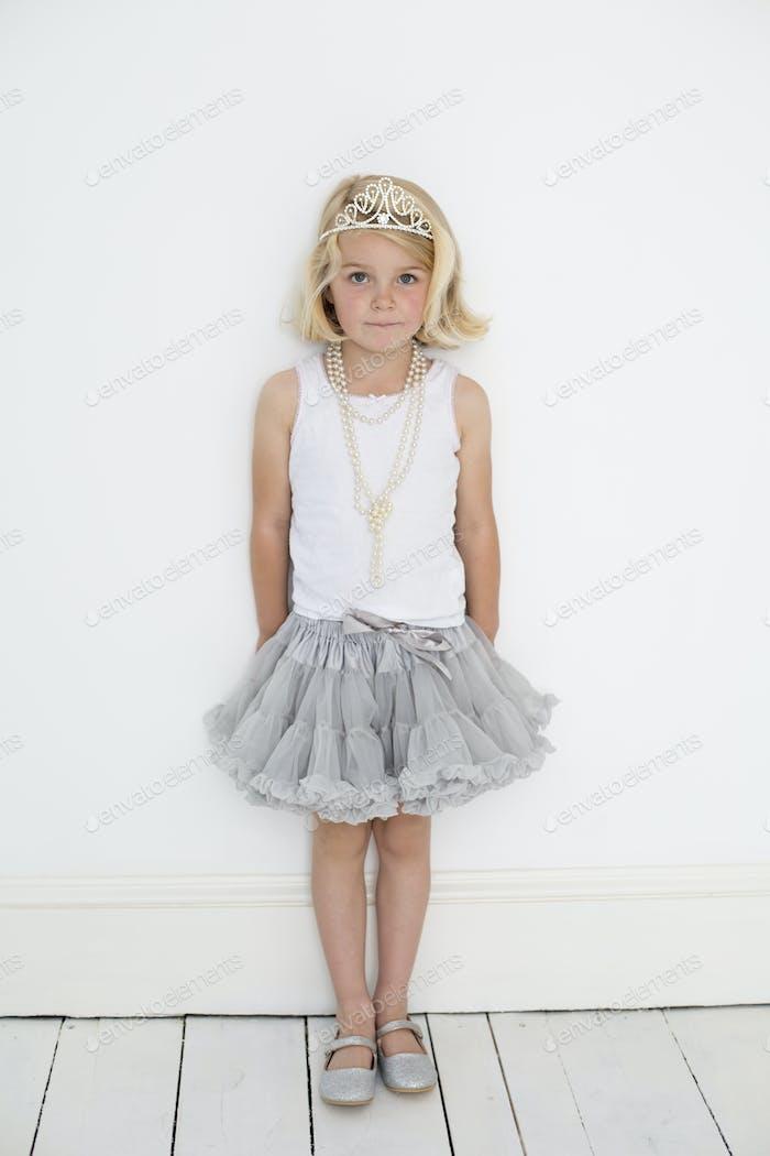 Junges Mädchen trägt eine Tiara und eine Perlenkette, posiert für ein Bild in einem Fotografen-Studio.