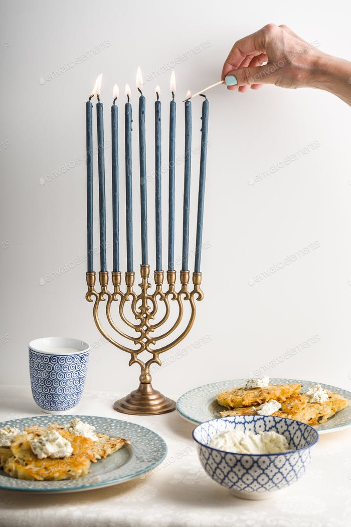 Hanukkah with lighted candles, latkes on a plate, curd cheese